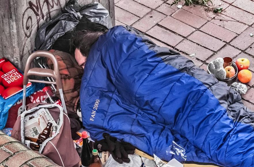Träumen von einem eigenen Herd. Obdachloser Mann am Hafen in Hamburg zur Weihnachtszeit.